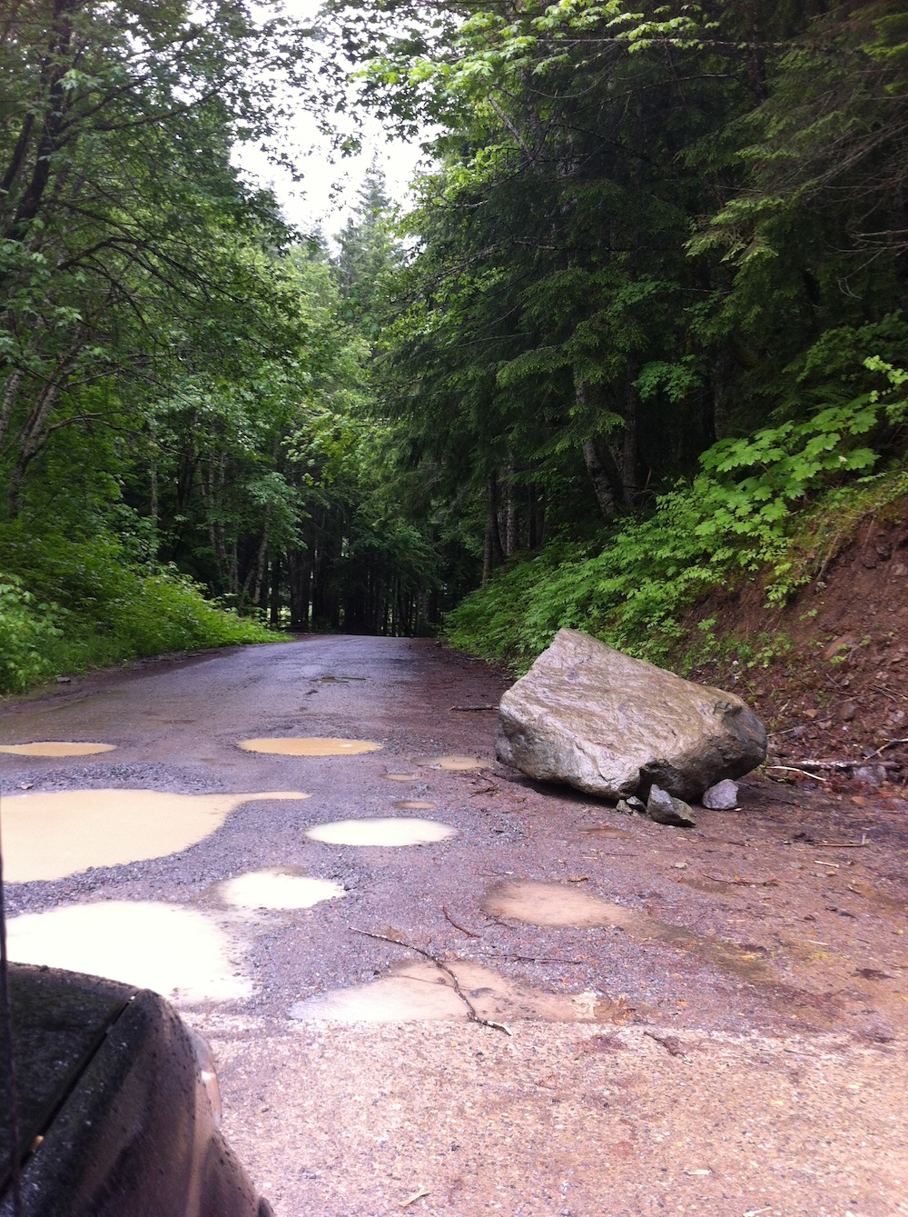 Road of pot holes full of rain along our drive up the mountain